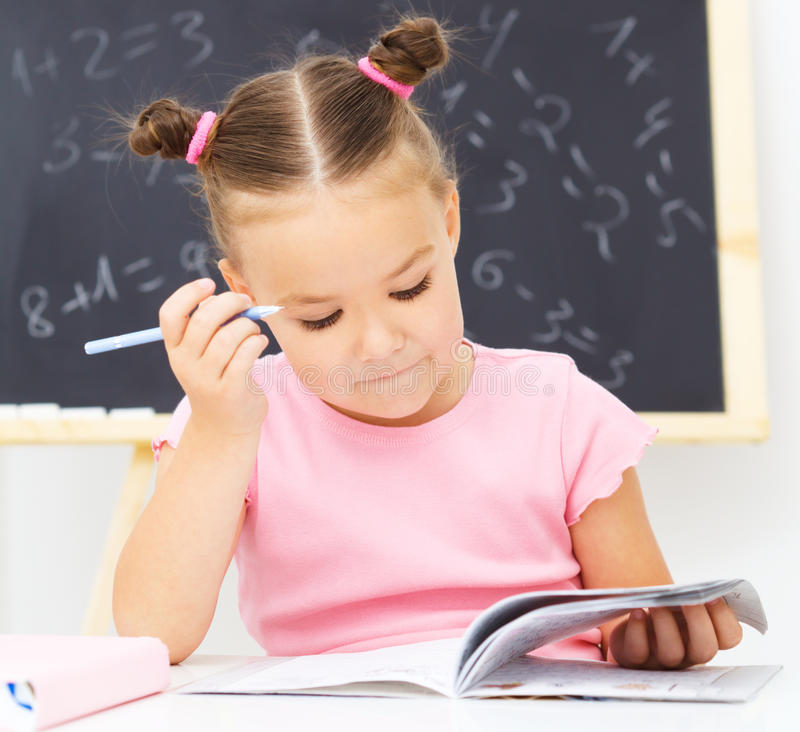 Little girl is writing using a pen royalty free stock photos