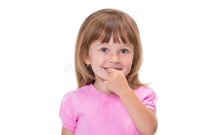 Cute little girl 3 year old in pink t-shirt holds fingers in mouth or bites nails isolated on white background. Bad childhood. Habits stock image