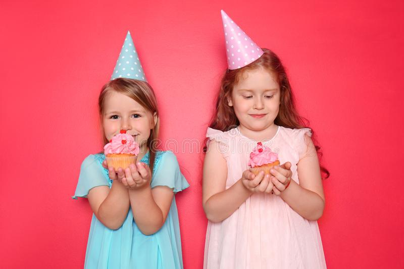 Cute little girls with Birthday caps eating cupcakes on color background stock photos