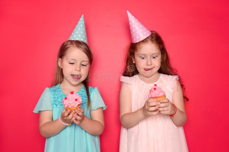 Cute little girls with Birthday caps eating cupcakes on color background stock images