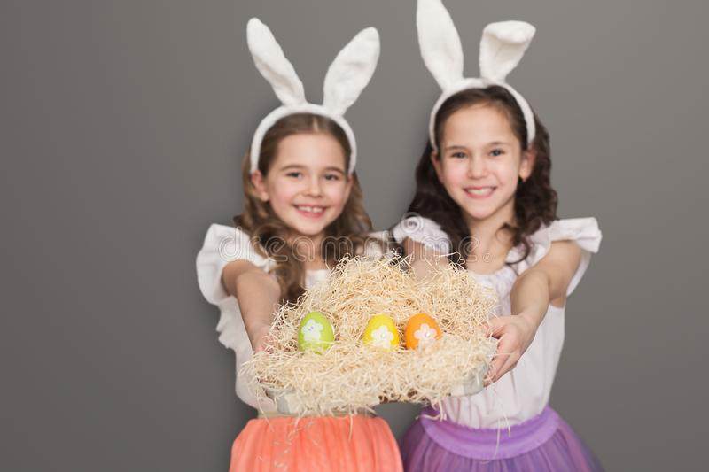 Cute little girls with bunny ears holding bright Easter eggs stock photo