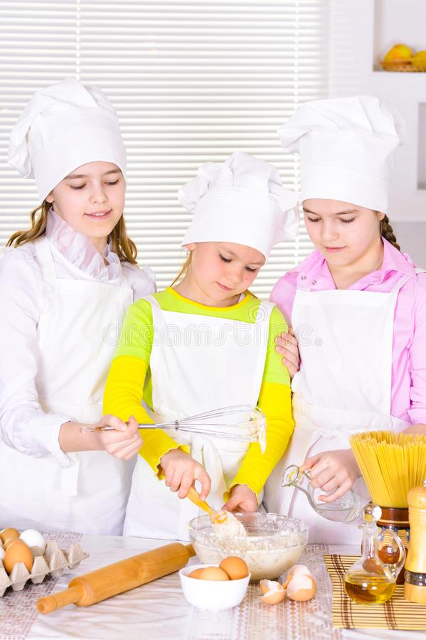 Cute little girls in chef`s hats and aprons preparing dough in the kitchen stock image