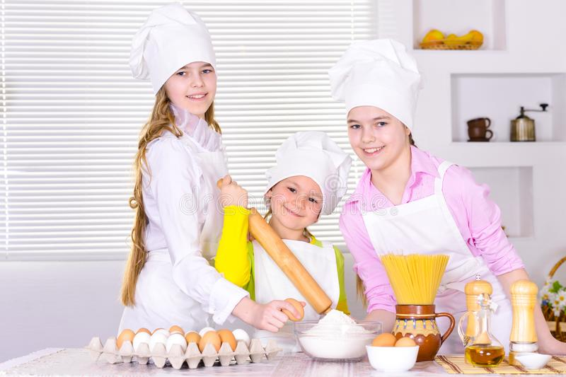 Cute little girls in chef`s hats and aprons preparing dough in the kitchen. At home royalty free stock image