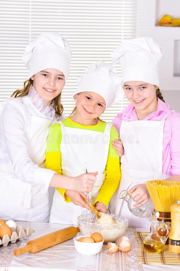 Cute little girls in chef`s hats and aprons preparing dough in the kitchen. At home stock image
