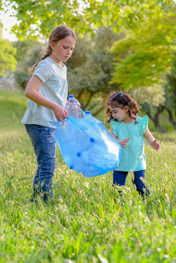 Kids cleaning in park.Volunteer children with a garbage bag cleaning up litter, putting plastic bottle in recycling bag. stock photography