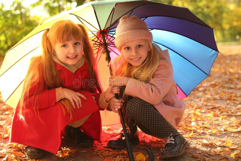 Cute little girls with colorful umbrella in autumn park royalty free stock photography