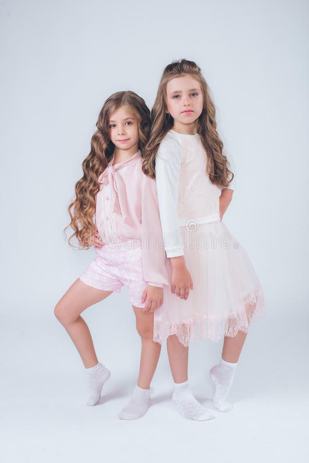 Cute little girls with curly hair in fashionable clothes of white and pink stock image