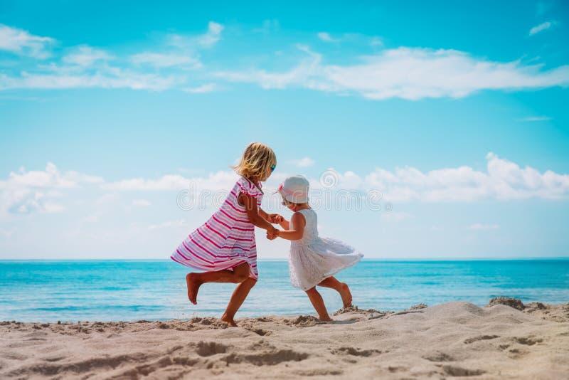 Cute little girls dance at beach, family enjoy tropical vacation. Cute happy little girls dance at beach, family enjoy tropical vacation stock photography