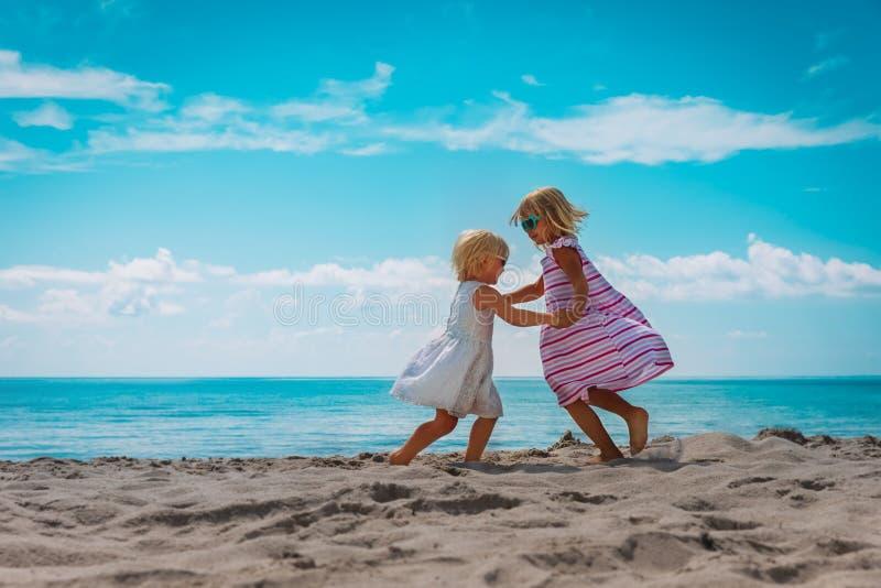 Cute little girls dance at beach, family enjoy tropical vacation. Cute little girls dance at beach, happy family enjoy tropical vacation royalty free stock photos