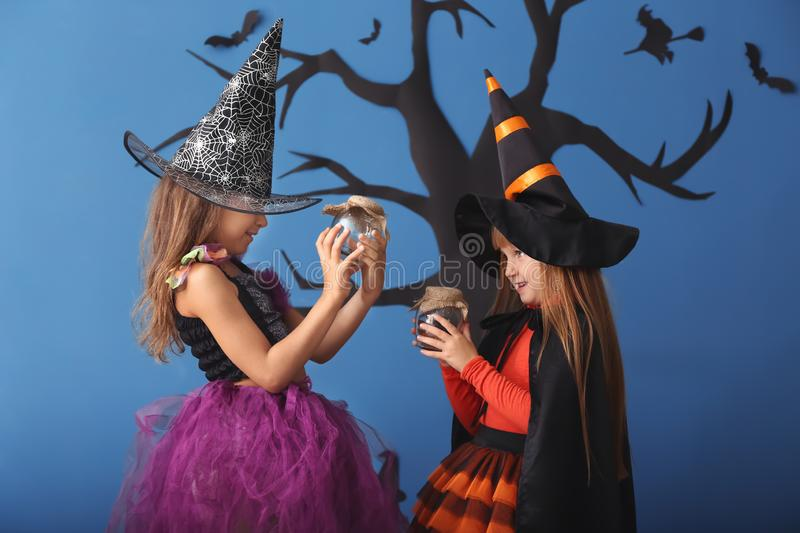 Cute little girls dressed as witches for Halloween standing against color wall with creepy decor stock image