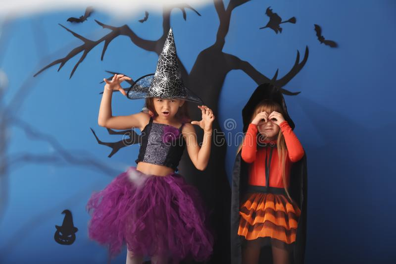 Cute little girls dressed as witches for Halloween standing against color wall with creepy decor royalty free stock image