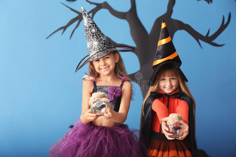 Cute little girls dressed as witches for Halloween standing against color wall with creepy decor royalty free stock photos