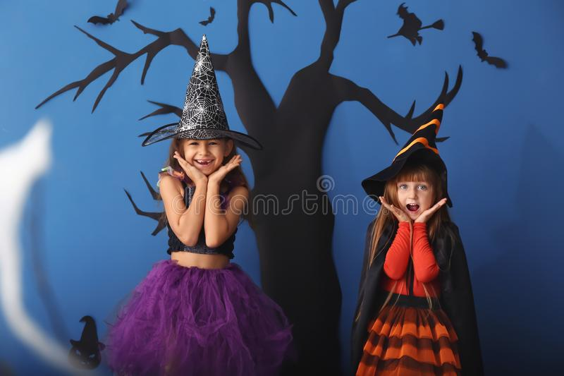 Cute little girls dressed as witches for Halloween standing against color wall with creepy decor stock images