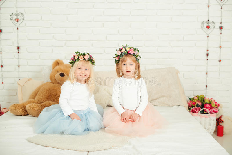 Cute little girls in dresses with flowers wreath on their head. Two little sisters sitting on the bed in white studio. stock photos
