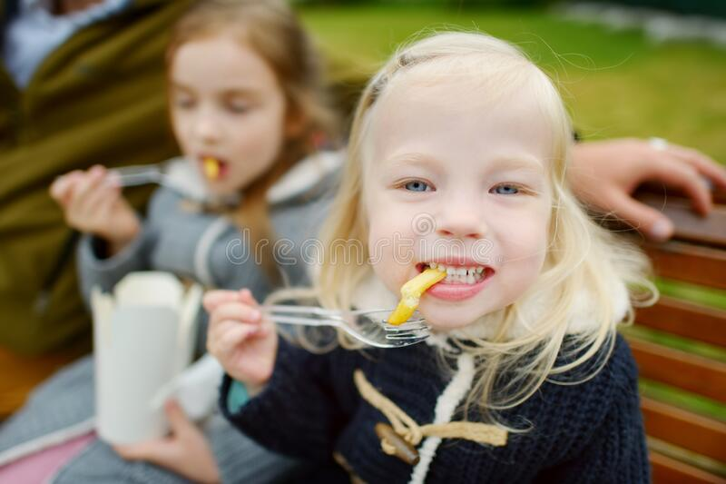 Cute little girls eating french fries on beautiful day outdoors. Snacks for kids royalty free stock images