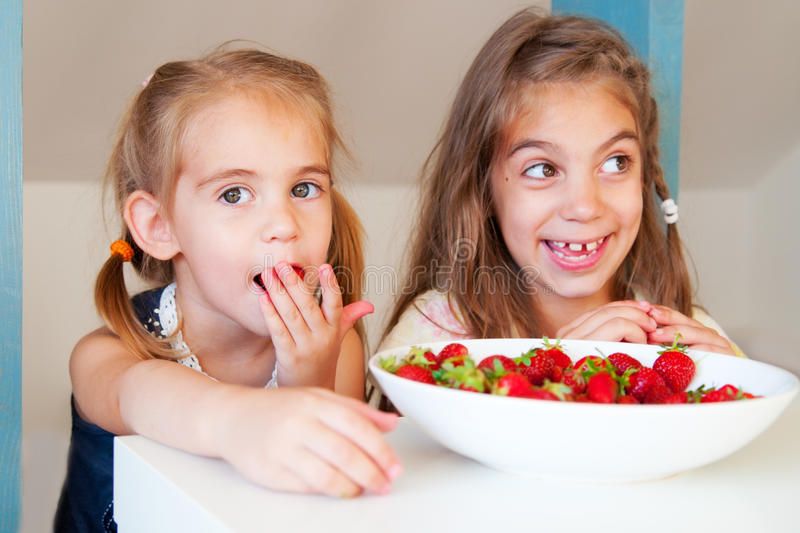 Cute little girls eating strawberry royalty free stock photo