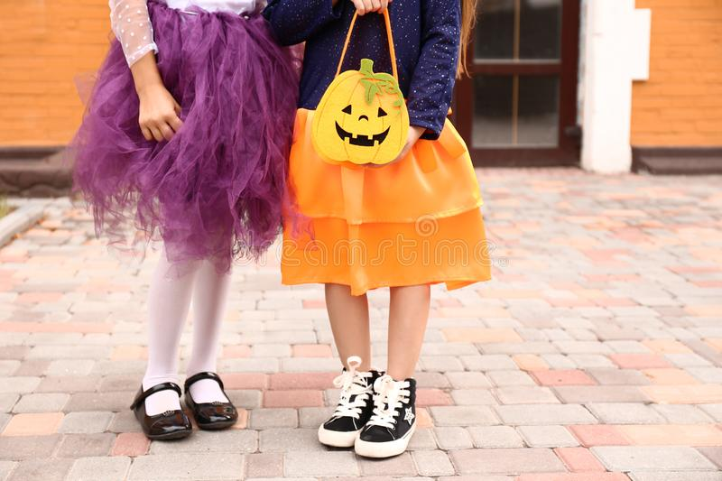 Cute little girls in Halloween costumes trick-or-treating outdoors royalty free stock images