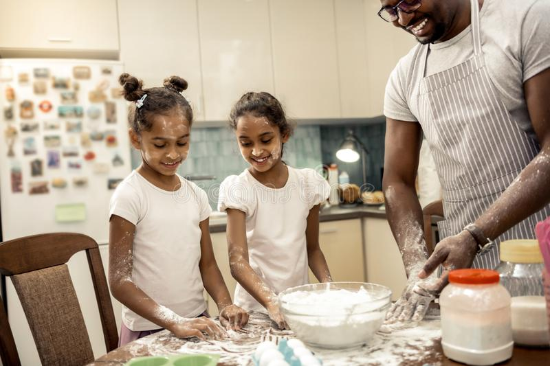 Cute little girls having flour on their faces and bodies while cooking. Flour everywhere. Cute little girls having flour on their faces and bodies while cooking royalty free stock photography