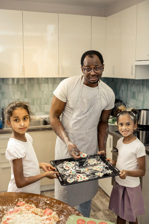 Cute little girls joining their father while putting cookies in to oven stock photography