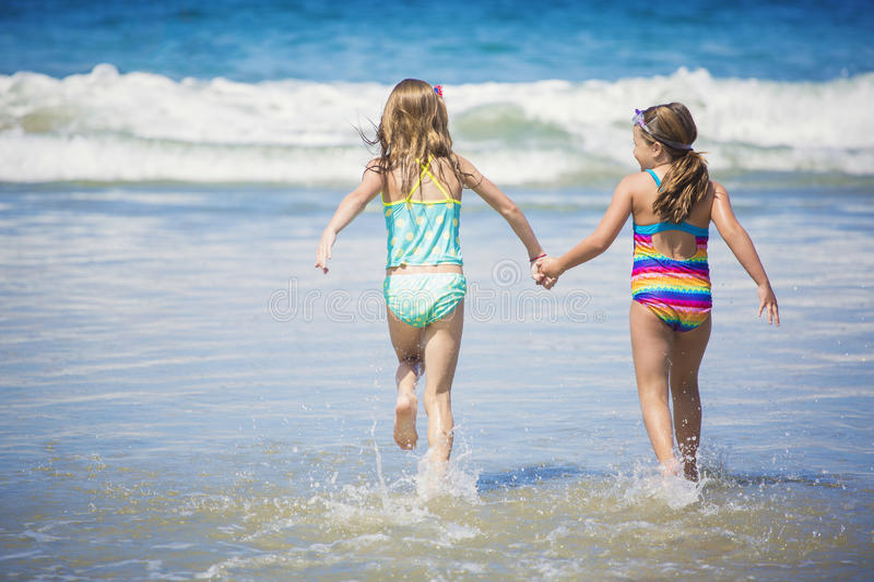 Cute little girls playing at the beach together during summer vacation stock image