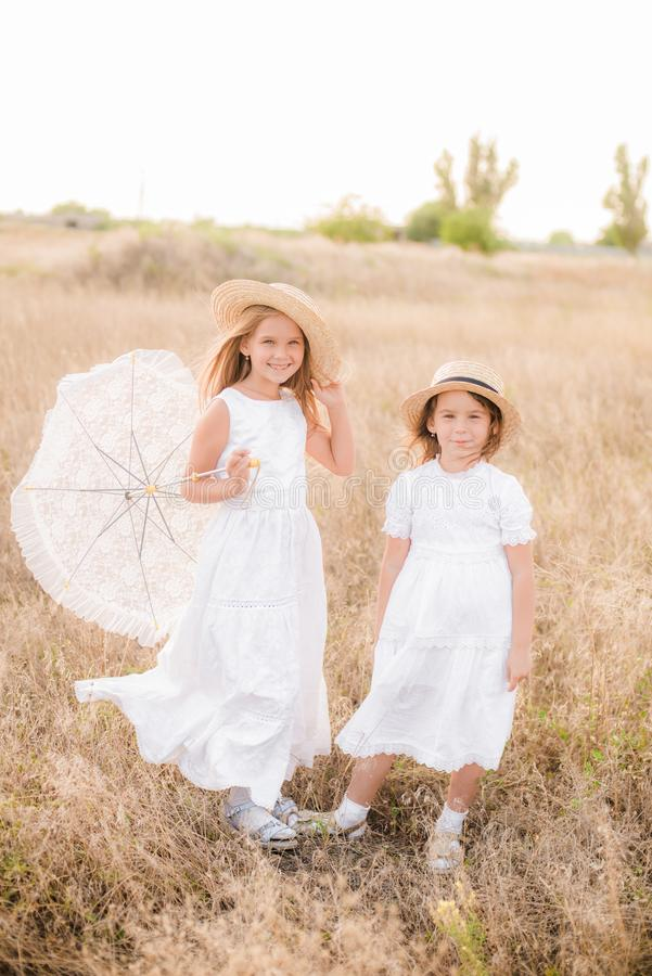 Free Cute Little Girls Sisters With Blond  Hair In A Summer Field At Sunset In White Dresses Royalty Free Stock Image - 152797716