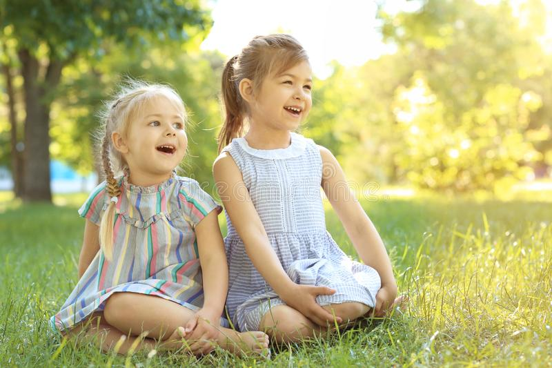 Cute little girls sitting on green grass royalty free stock photos