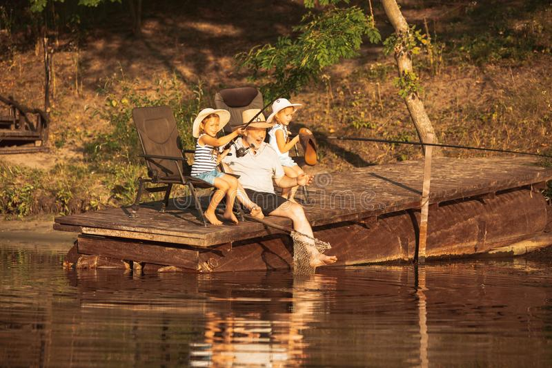 Cute little girls and their granddad are on fishing at the lake or river royalty free stock photography