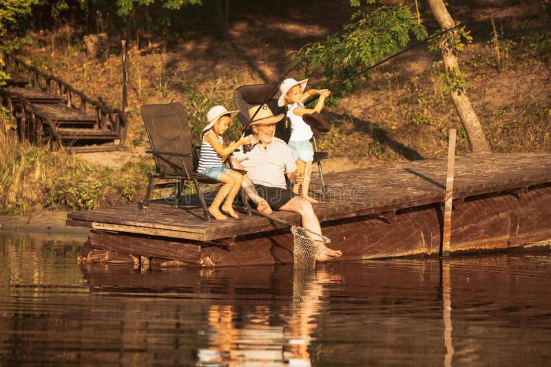 Cute little girls and their granddad are on fishing at the lake or river royalty free stock images