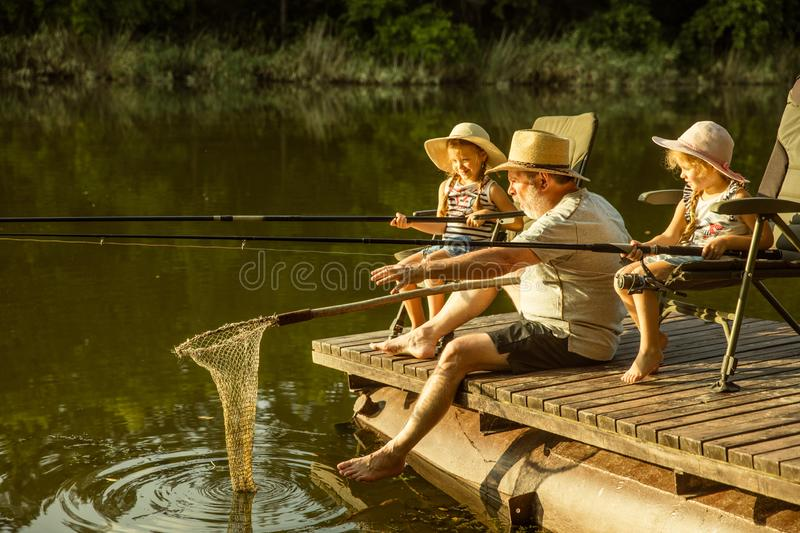 Cute little girls and their granddad are on fishing at the lake or river royalty free stock image