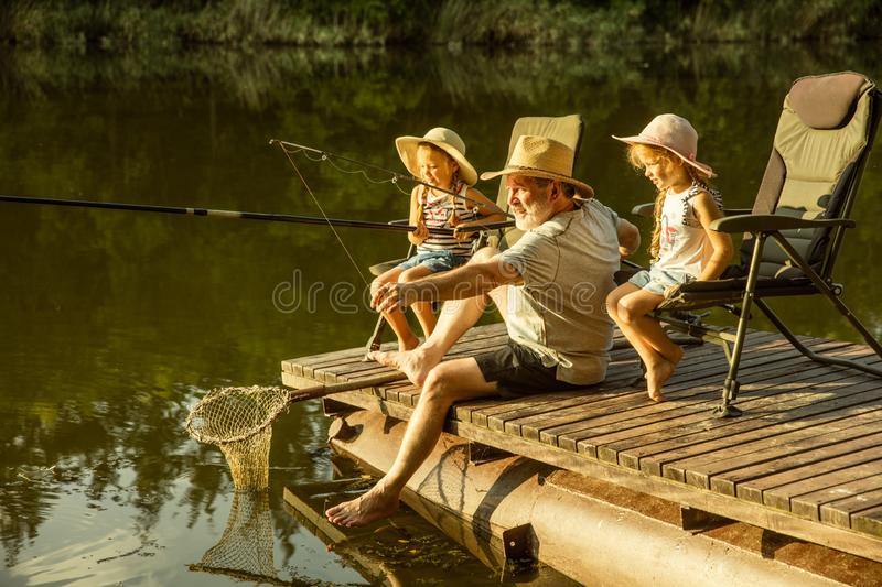 Cute little girls and their granddad are on fishing at the lake or river stock photo