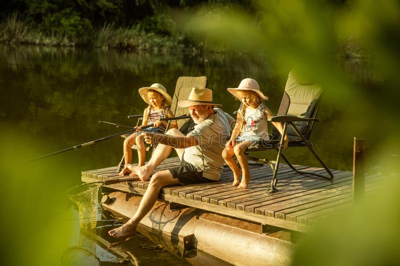 Cute little girls and their granddad are on fishing at the lake or river stock photos