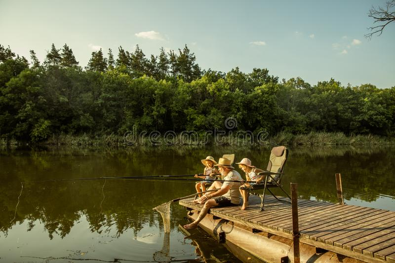 Cute little girls and their granddad are on fishing at the lake or river royalty free stock photo