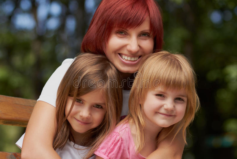 Cute little girls with their mom outdoors royalty free stock photography