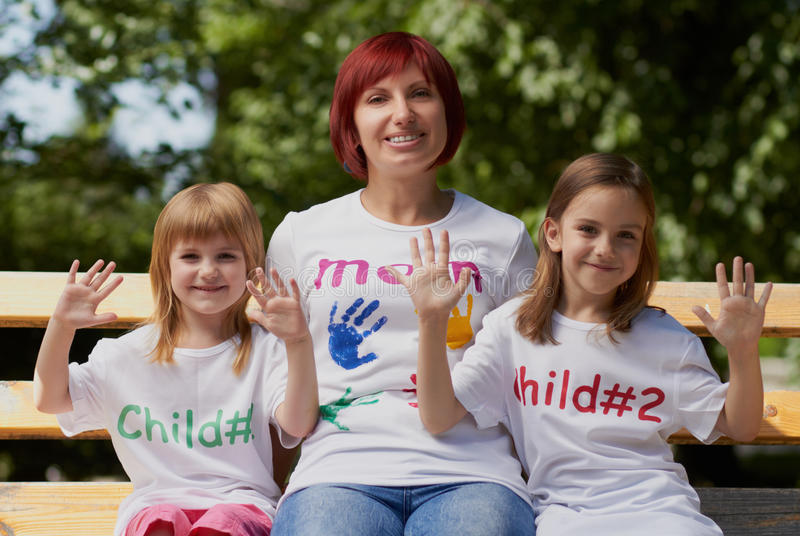 Cute little girls with their mom outdoors stock image