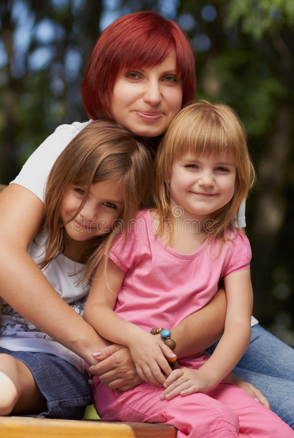 Cute little girls with their mom outdoors stock photos