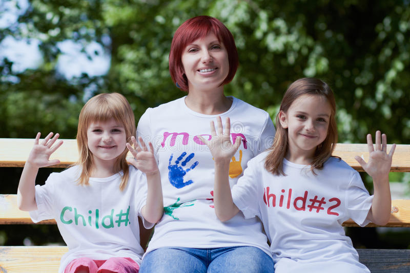Cute little girls with their mom outdoors stock photo