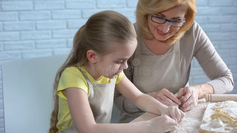 Cute little grandchild studying cook, helping grandmother, homemade patty royalty free stock photography
