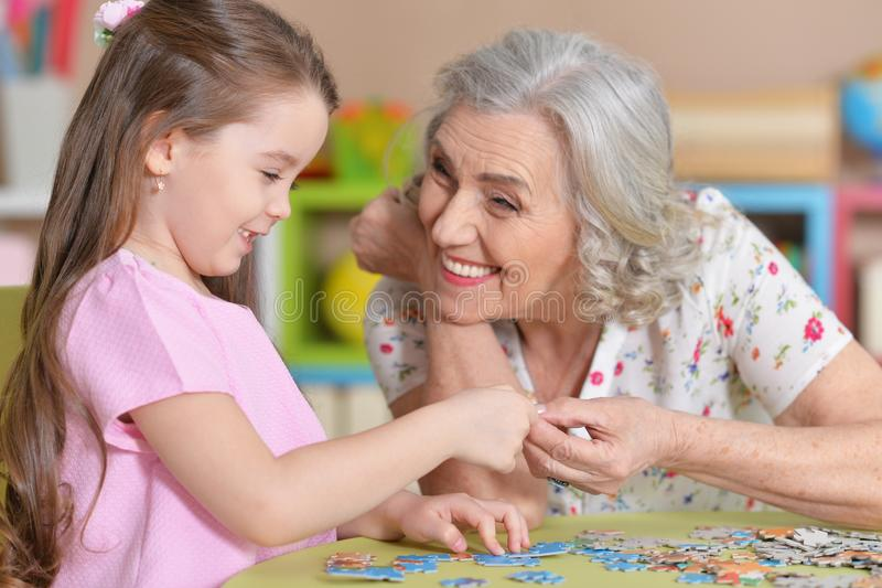 Cute little granddaughter and grandmother collecting puzzles. Together at home royalty free stock photo