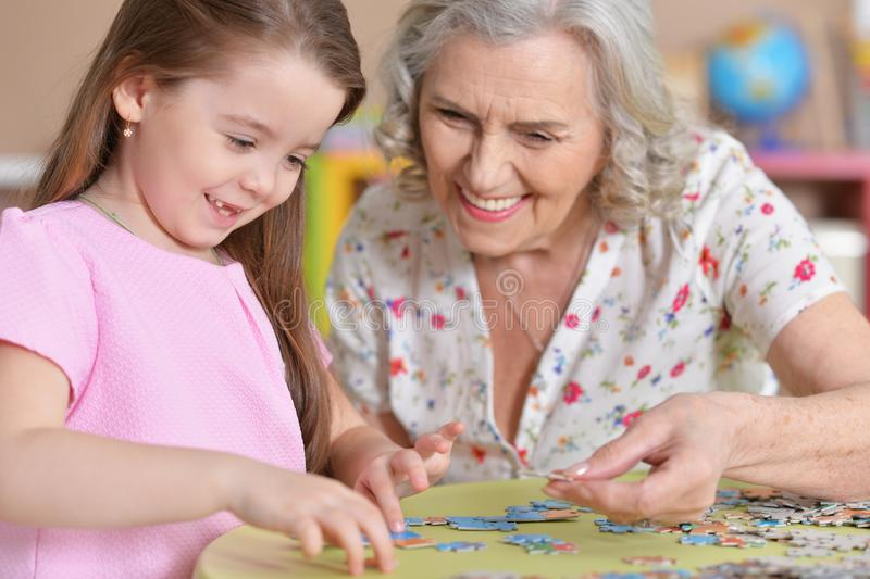 Cute little granddaughter and grandmother collecting puzzles. Together at home stock image