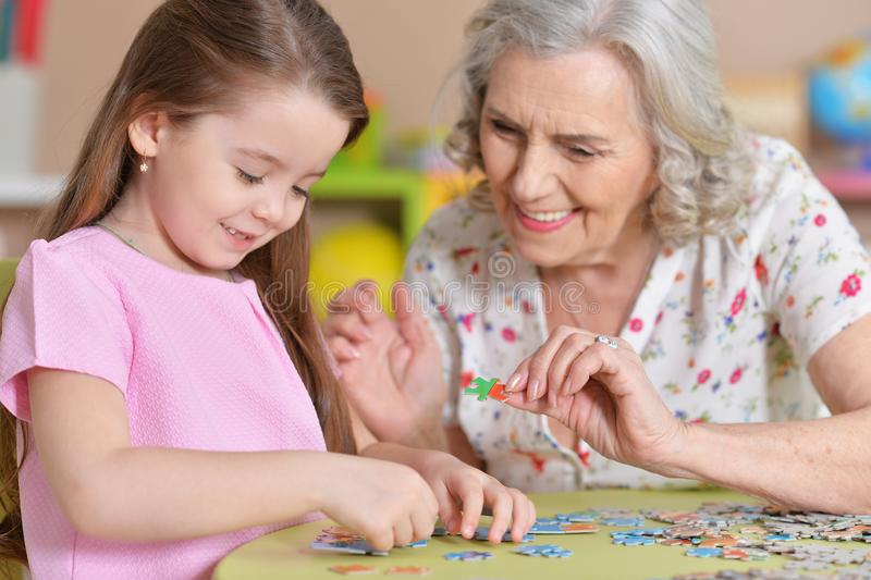 Cute little granddaughter and grandmother collecting puzzles. Together at home royalty free stock photography
