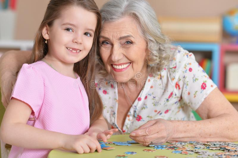 Cute little granddaughter and grandmother collecting puzzles. Together at home stock photography