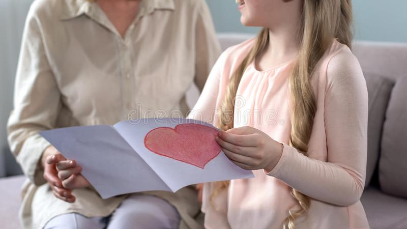 Cute little granddaughter presenting handmade greeting card to grandma, birthday. Stock photo stock images
