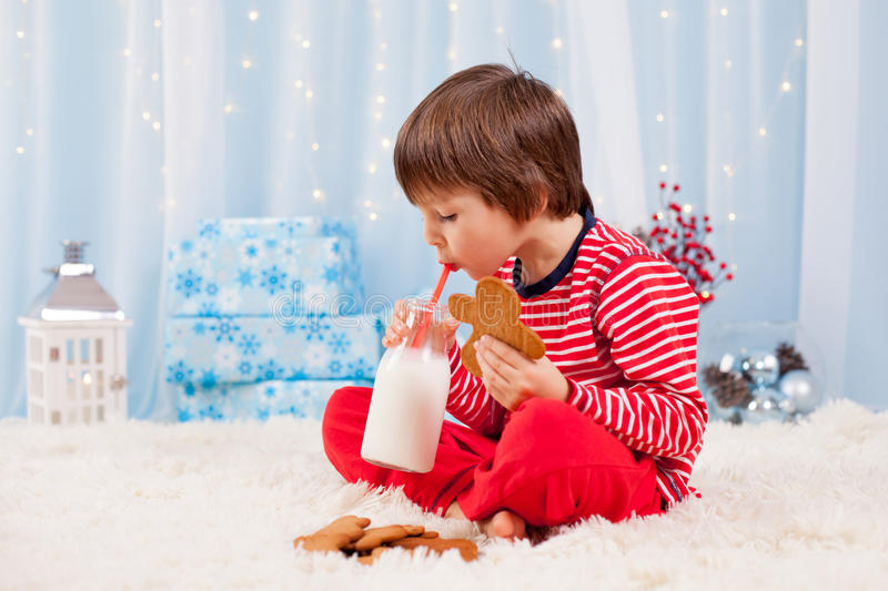 Cute little happy boy, eating cookies and drinking milk, waiting. For Santa in pajama on Christmas Eve night royalty free stock image