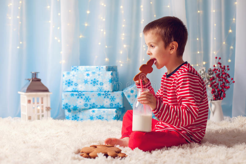 Cute little happy boy, eating cookies and drinking milk, waiting. For Santa in pajama on Christmas Eve night stock photos