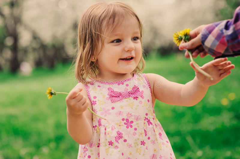 Cute little happy toddler girl portrait walking in spring or summer park stock photos
