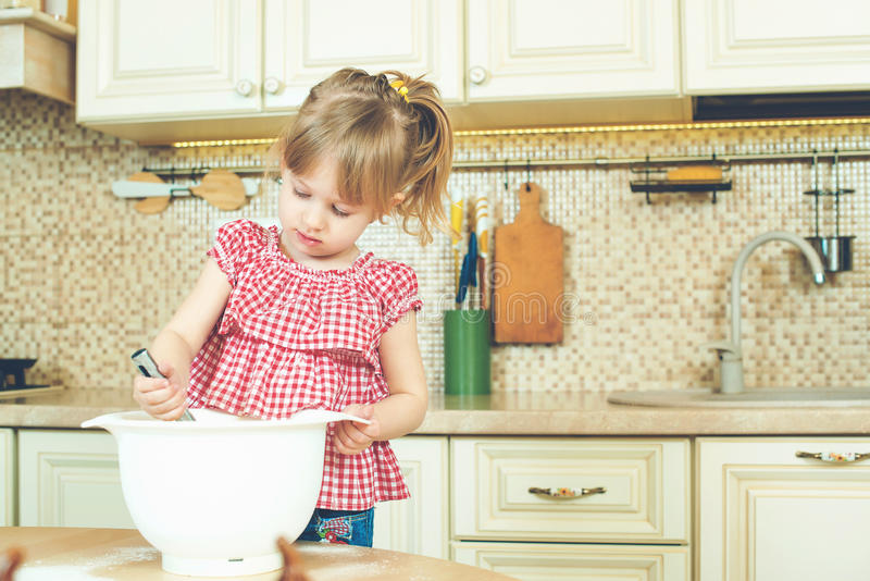 Cute little helper girl helping her mother cooking in a kitchen. Happy loving family are preparing bakery. Cute little helper girl helping her mother cooking in stock photography