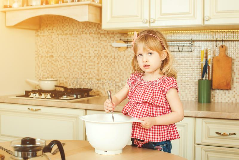 Cute little helper girl helping her mother cooking in a kitchen. Happy loving family are preparing bakery. Cute little helper girl helping her mother cooking in stock photo