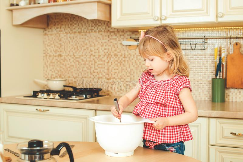 Cute little helper girl helping her mother cooking in a kitchen. Happy loving family are preparing bakery. Cute little helper girl helping her mother cooking in stock photos