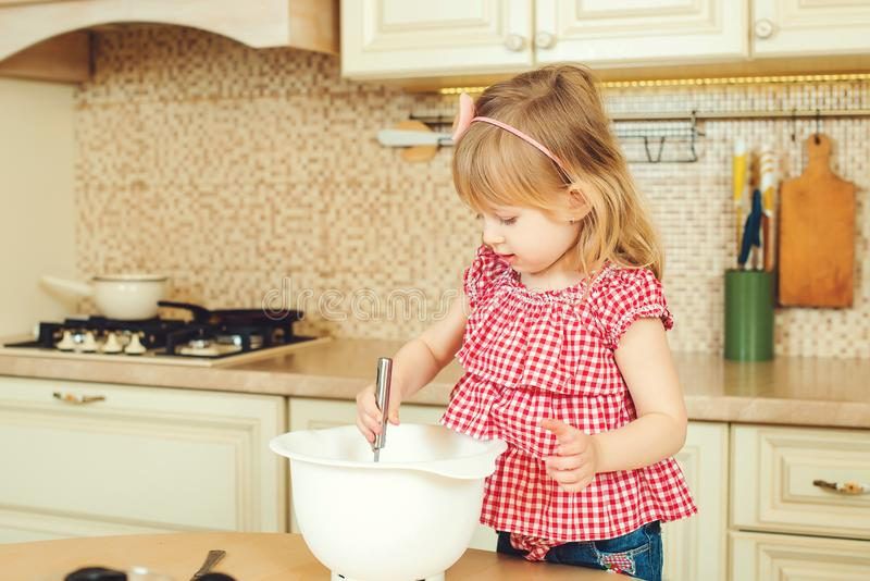 Cute little helper girl helping her mother cooking in a kitchen. Happy loving family are preparing bakery. Cute little helper girl helping her mother cooking in royalty free stock photography