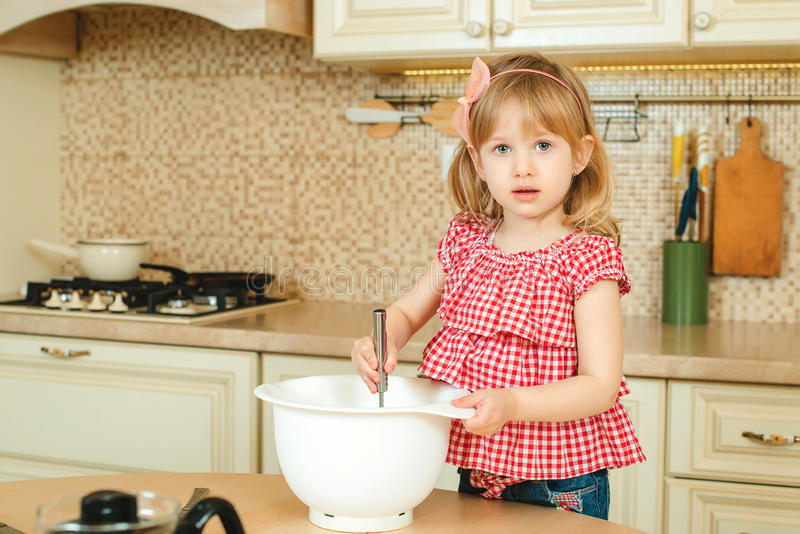 Cute little helper girl helping her mother cooking in a kitchen. Happy loving family are preparing bakery. royalty free stock photography